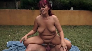 Busty redhead granny dickriding outdoors